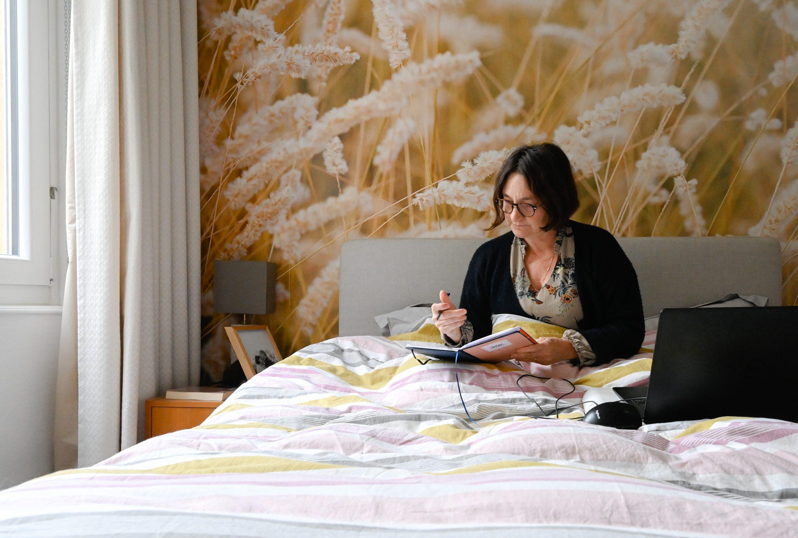 femme travail à l'ordinateur de son lit