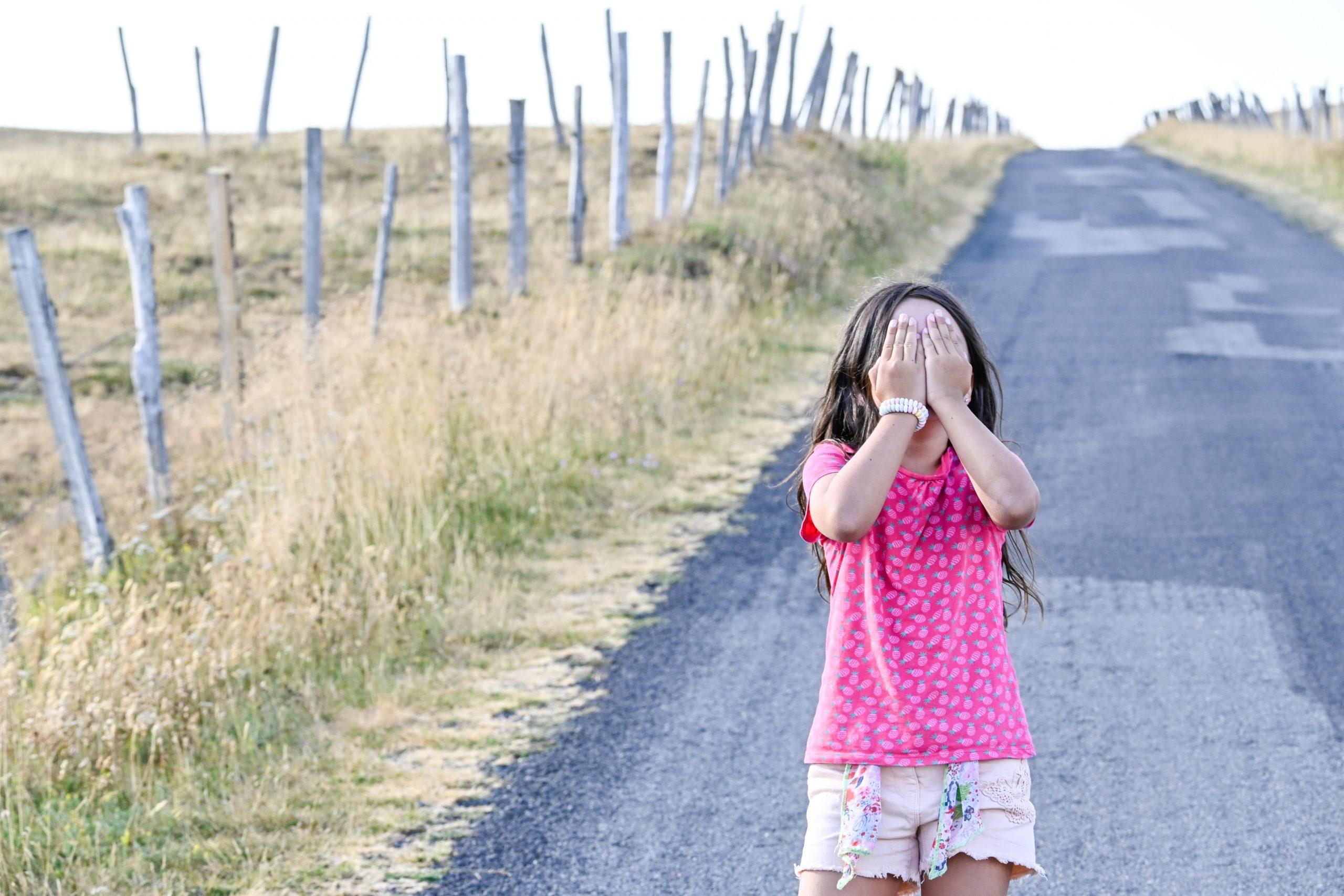 portrait sensible jeune fille sur uen route de montagne qui se cache le visage dans les mains